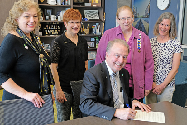 Mayor Mahoney signs the Daughters of the American Revolution Day proclamation as members of the Dacotah Chapter of DAR watch