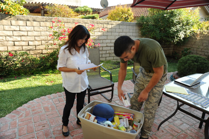 A military couple load their emergency kit on their patio.